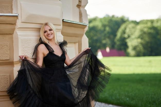Стильная счастливая женщина на открытом воздухе в черном платье, улыбаясь в камеру