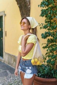 イタリアの小さな町の通りを歩いているスタイリッシュな幸せな女性