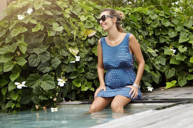 Стильная счастливая молодая беременная женщина в темных тонах отдыхает на открытом воздухе у бассейна, ее ноги болтаются в голубой воде