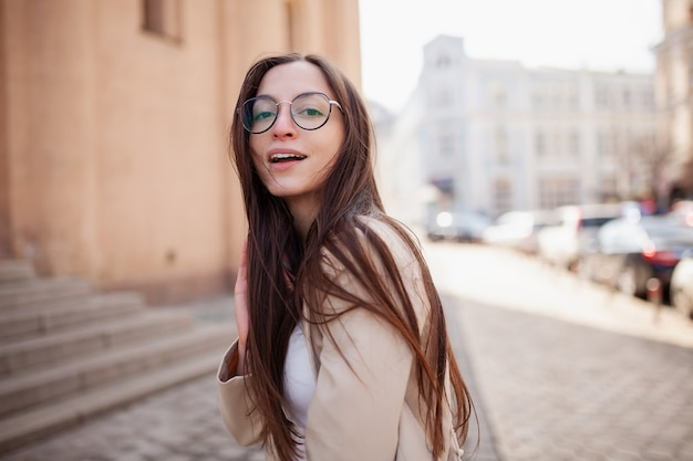 Stylish happy young woman in a jacket portrait of a smiling girl in glasses for sight on the street in the city center