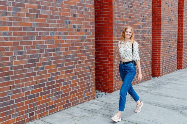 街の通りでポーズをとって金髪のスタイリッシュな幸せな若い女性