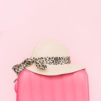 Stylish hat on plastic luggage travel bag against pink background