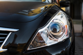 Stylish headlight of dark auto parked on street