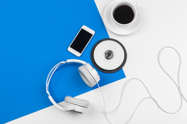 Stylish headphones on blue and white color, top view.