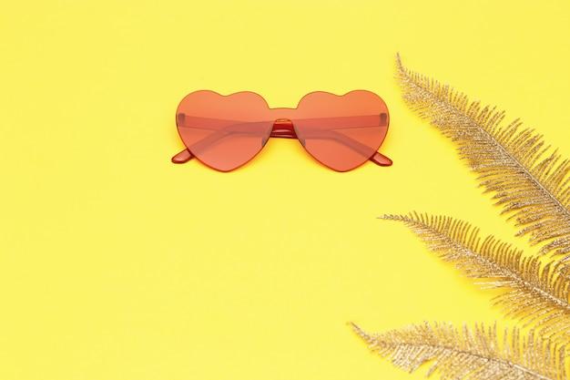 세련 된 심장 모양의 안경 및 복사 공간 종이 배경에 황금 야 자 잎. 아름 다운 유행 선글라스 붉은 색. 패션 여름 개념입니다. 평평하다.