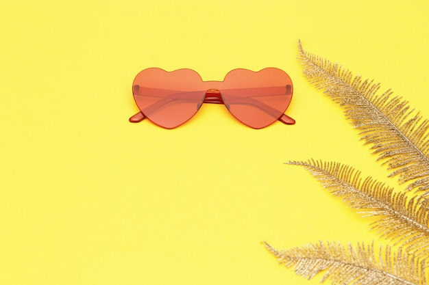 Stylish heart shaped glasses and golden palm leaves on paper background with copy space. beautiful trendy sunglasses red colored. fashion summer concept. flat lay.