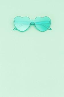 세련 된 심장 모양의 복사 공간 민트 녹색 색된 배경에 안경. 아름다운 유행 선글라스. 패션 여름 개념입니다.