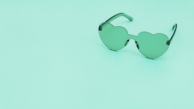 세련 된 심장 모양 복사 공간 종이 배경에 안경. 아름다운 유행 청록색 선글라스. 패션 여름 개념입니다.