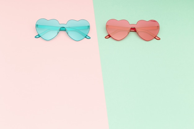 Stylish  heart shaped glasses on paper background with copy space.  beautiful trendy sunglasses. fashion summer concept. flat lay.