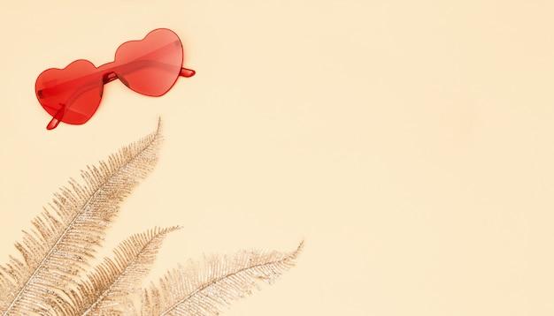 황금 종 려 잎으로 세련 된 심장 모양의 안경