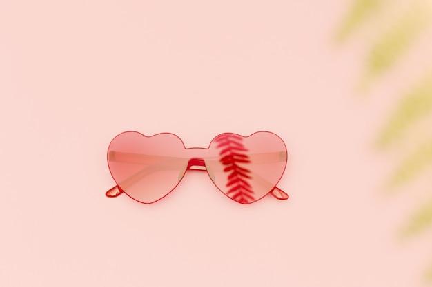 손바닥에서 그림자와 함께 세련된 심장 모양의 안경은 분홍색에 나뭇잎