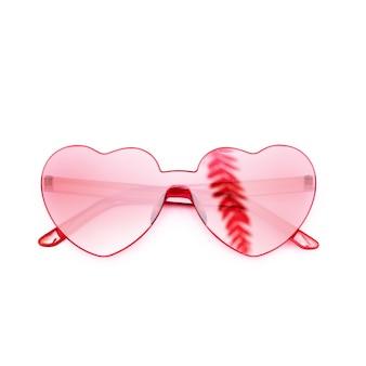 야자수 잎에서 그림자가있는 세련된 심장 모양의 안경, 트렌디 한 빨간색 선글라스.