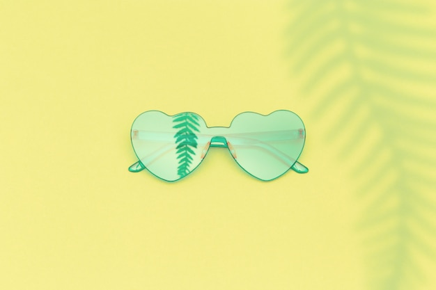 Stylish heart shaped glasses with shadow of palm leaves on yellow background with copy space.  beautiful trendy green sunglasses.
