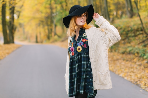 Stylish hippie girl in a knitted sweater and hat walks in the autumn park.