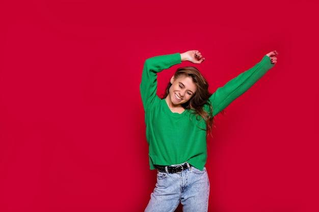 Elegante ragazza hippie su rosso che tira su le mani, celebra il nuovo anno, indossa un maglione verde e jeans, felice festa in discoteca di carnevale, coriandoli scintillanti, tiene il bicchiere, divertendosi