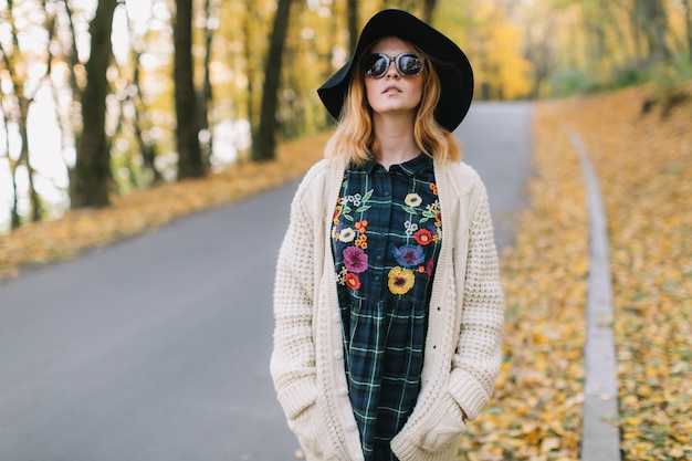 Stylish hippie girl in a sunglasses, knitted sweater and hat walks in the autumn park.