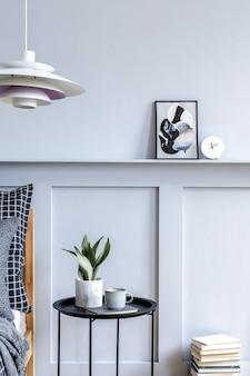 디자인 가구가있는 세련된 힙 스터 침실 인테리어, 포스터 프레임, 책, 시계, 장식, 아름다운 침대 시트, 담요 및 베개를 현대 가정 장식으로 모의하십시오.