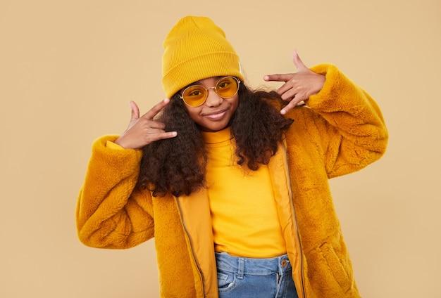 Стильная хипстерская черная кудрявая девушка в модных очках и яркой красочной теплой одежде и шляпе делает рок-жест, стоя на бежевом фоне