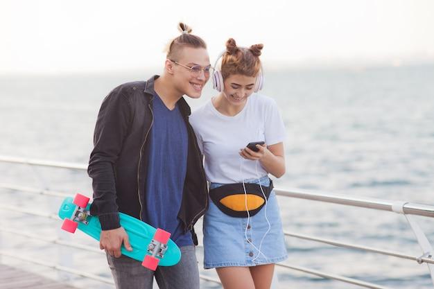 ビーチの遊歩道を散歩し、ヘッドフォンで音楽を聴く愛のスタイリッシュな流行に敏感なカップル。