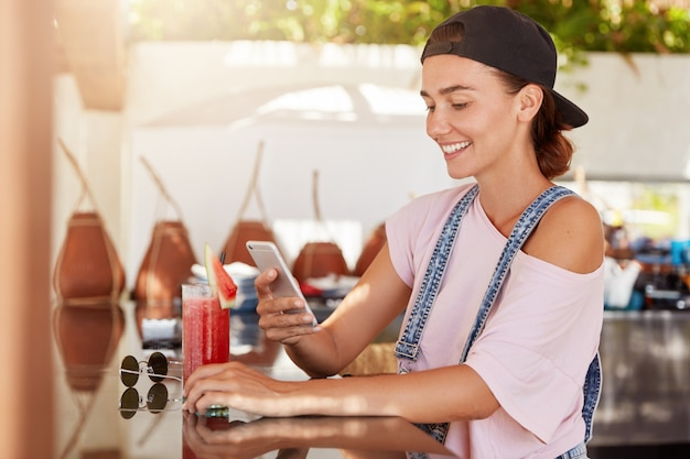 Stylish hipster female in cap, being glad to receive text message on mobile phone, surfes internet in cozy cafe during summer recreation, drinks smoothie, wears fashionable clothing. people and style