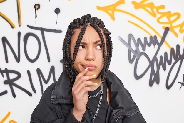 Stylish hipster girl has dreadlocks being deep in thoughts keeps hand near mouth concentrated above poses in urban environment against graffiti wall wears black jacket