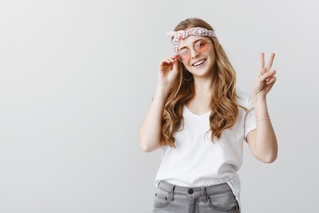 Стильная хипстерская девушка в солнцезащитных очках улыбается счастливой, показывая знак мира