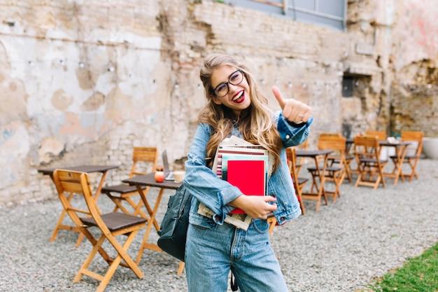 古いレンガの壁の前でポーズレトロなジーンズスーツでスタイリッシュな内気な少女。古い建物の横にバッグ立ってトレンディな若い女性。