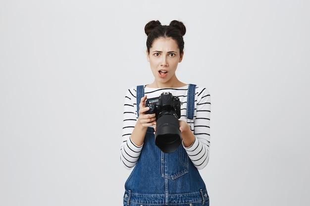 スタイリッシュな流行に敏感な女の子、カメラを保持している写真家