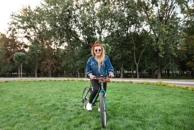 スタイリッシュな内気な少女が公園の緑の芝生で自転車に乗る
