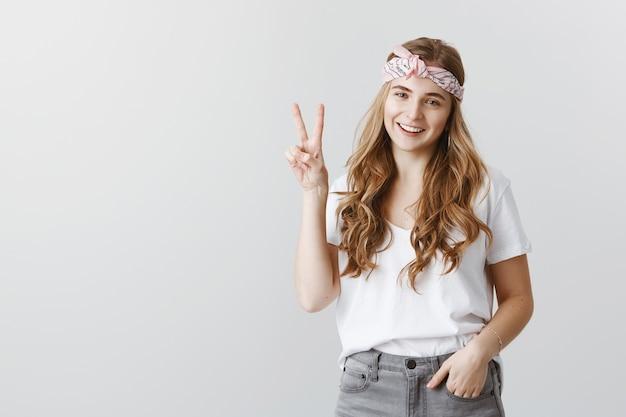 Ragazza alla moda hipster in occhiali da sole sorridendo felice, mostrando il segno di pace