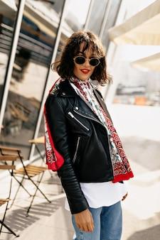 Ragazza alla moda hipster che indossa giacca di pelle con acconciatura corta e rossetto rosso che cammina in città alla luce del sole