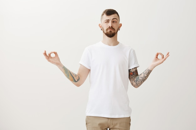 Stylish hipster guy trying meditate, peeking left at bothering sound