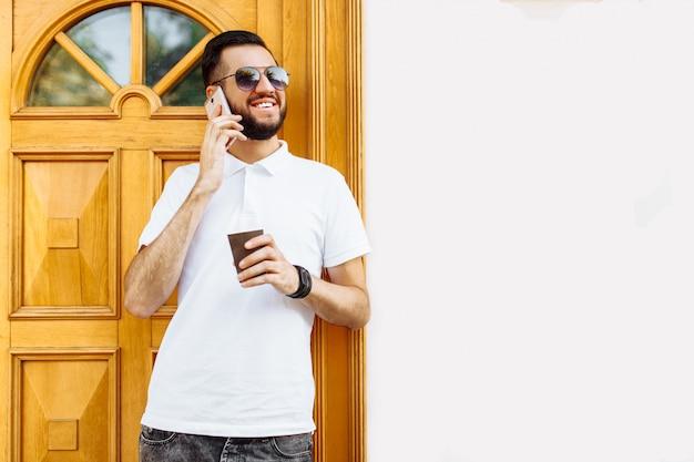白いシャツとサングラス、電話で話しているとコーヒーを飲む白い建物の壁にスタイリッシュなヒップスター