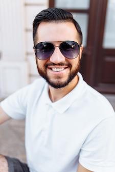 白いtシャツとひげのスタイリッシュなヒップスター、白い木製の壁の近くに立っています。