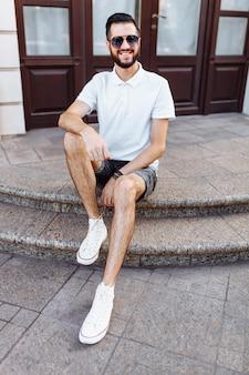 白い建物の近くの階段に座っているひげのある白いtシャツを着たスタイリッシュなヒップスター