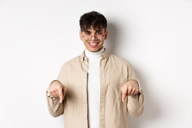 Stylish hipster male model in glasses pointing fingers down, smiling pleased at camera, recommending product, standing on white background.