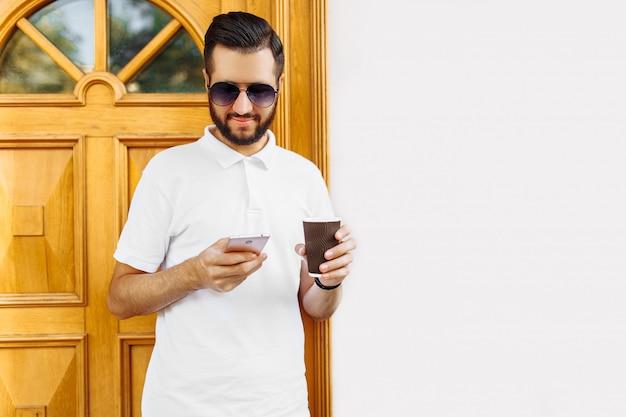 スマートフォンを押しながらコーヒーを飲みながら白い建物の壁に、ひげと白いシャツを着たスタイリッシュなヒップスター