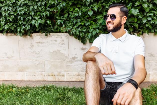 ひげと白いtシャツを着たスタイリッシュなヒップスター。落葉性の緑の壁にある芝生の上に座っています。
