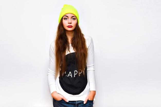 Стильная хипстерская женщина позирует на фоне белой стены, зимнее время, свитер, неоновая шляпа и джинсы, повседневная модная спортивная одежда, длинные волосы, яркий макияж, вспышка, серьезное сексуальное лицо.