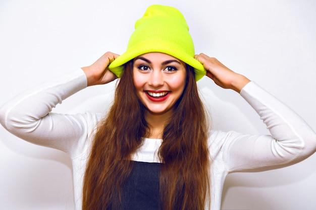 Donna alla moda hipster in posa contro il muro bianco, orario invernale, maglione, cappello al neon e jeans, abbigliamento sportivo alla moda casual, capelli lunghi, trucco luminoso, flash, viso sexy serio.