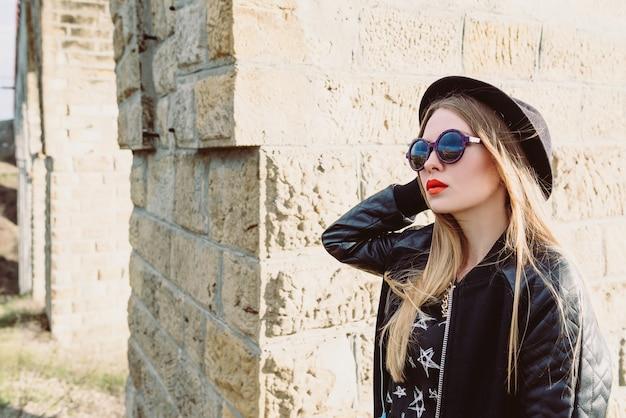 Стильная хипстерская женщина-путешественница в солнцезащитных очках и черной шляпе у виадука моста путешествие по европе