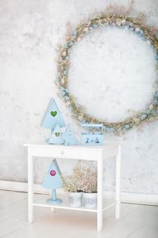 파란색의 세련된 가정 장식은 나무 바구니, 장식 상자 및 귀여운 토끼입니다. 부활절 장식. 흰색 테이블에 나무 둥지 상자 여름 마 구성. 봄 방 장식
