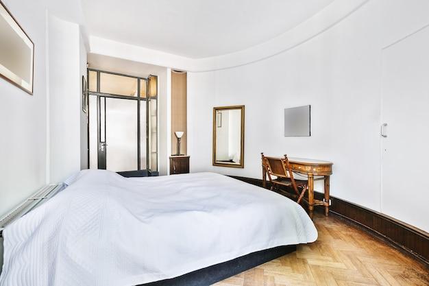 Стильный домашний интерьер спальни с необычной изогнутой архитектурой и белыми стенами с кроватью и винтажным деревянным столом со стулом.