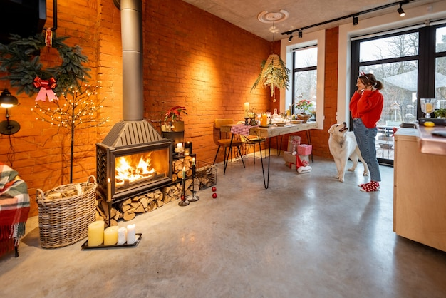 お祝いに装飾されたダイニングテーブルと暖炉のあるスタイリッシュな家のインテリア。年末年始に犬を連れた女性