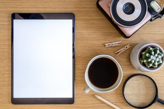 モックアップタブレット画面、事務用品、一杯のコーヒー、電話、写真カメラ、植物、ビジネスコンセプトのパーソナルアクセサリーのスタイリッシュなホームオフィス構成。