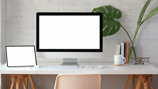 Stylish home office with blank screen desktop computer