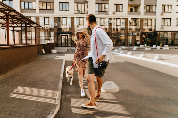 Stylish husband and wife in summer outfits run and play with their dog on background of apartment house. man in light shirt holds his beloved hand and carries camera.