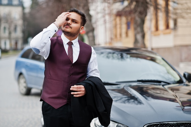 Stylish indian businessman in formal wear vest suit standing against black business car on street of city.