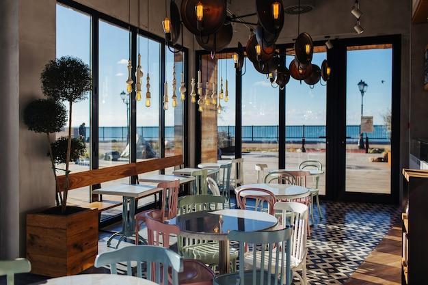 Стильное интерьерное кафе в винтажном стиле, с большими окнами и видом на море.