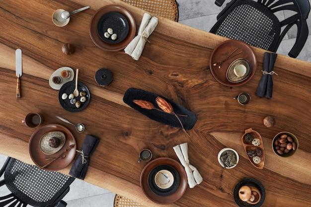 Стильный интерьер столовой с деревянным столом из орехового дерева, ретро стульями, посудой, тарелками, скатертью, чайником, продуктами, украшениями и элегантными аксессуарами. цементный пол. шаблон. вид сверху.